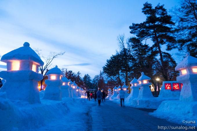 上杉神社前の参道に並ぶ雪灯篭